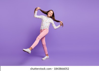 Full length body size photo little girl smiling happily keeping long hair tails kicking dancing isolated on bright violet color background