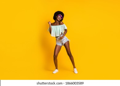 Full length body size photo of black skinned woman dancing on weekend wearing star shaped sunglass isolated on vibrant yellow color background