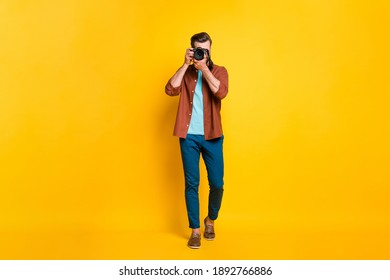 Full length body size photo of bearded millennial taking photo with professional camera isolated on bright yellow color background