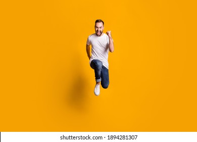 Full length body size photo of jumping cheerful male model running fast on sale isolated vibrant yellow color background