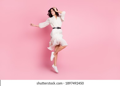 Full length body size photo of cheerful woman in long dress jumping looking empty space isolated pastel pink color background