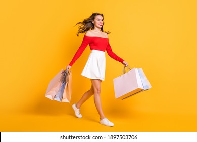Full length body size photo girl smiling looking blank space stepping with packages from store isolated on bright yellow color background