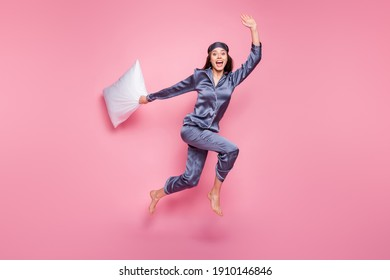Full length body size photo of girl wearing pajama waving hand with pillow in morning late isolated on pastel pink color background