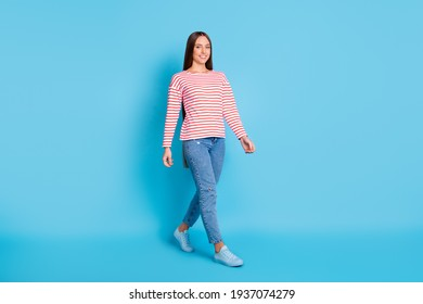 Full length body size photo walking girl wearing stylish outfit smiling isolated on bright blue color background