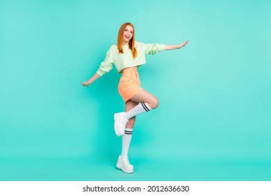 Full length body size photo of pretty red haired girl laughing wearing stylish clothes isolated on vivid turquoise color background