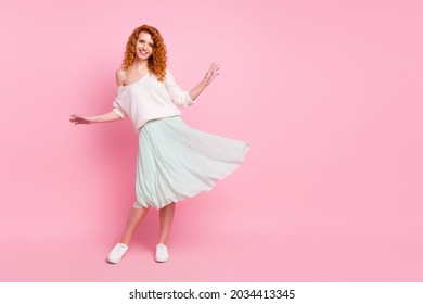 Full length body size photo of with red hair woman smiling wearing stylish spring clothes isolated on pastel pink color background