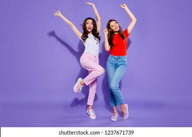 Full length body size portrait of two crazy nice girlish childish careless carefree sweet lovely attractive cheerful funny positive girls raising hands up isolated over violet purple pastel background