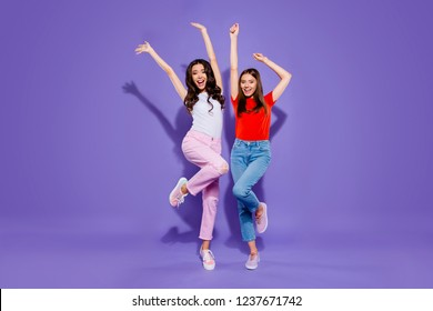 Full length body size portrait of two childish careless carefree sweet lovely attractive cheerful cheery funny positive girls raising hands up having fun isolated over violet purple pastel background