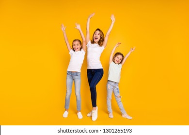Full length body size portrait of three nice lovely slim attractive cheerful cheery positive ecstatic people having fun raising hands up isolated over bright vivid shine yellow background