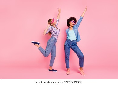 Full length body size portrait of two person nice cool crazy careless attractive charming cheerful cheery playful girls wearing casual checkered shirt having fun isolated over pink pastel background