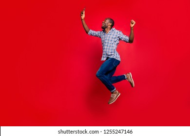 Full length body size profile side view of nice funny crazy handsome cheerful guy wearing checkered shirt holding in hands cell reading text going in air isolated on bright vivid shine red background