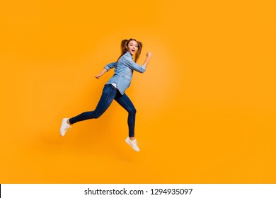 Full length body size profile side view of nice lovely careless carefree attractive slim sporty fit cheerful school girl running to cool party in air isolated over bright vivid shine yellow background