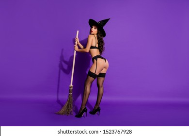 Full length body size profile side view of nice attractive brunette alluring wavy-haired girl teasing posing with broom isolated on bright vivid shine vibrant violet purple lilac color background