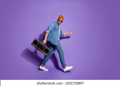 Full length body size profile side photo of carefree moving attractive handsome guy holding sound recorder with hands going to discotheque isolated over purple bright color background