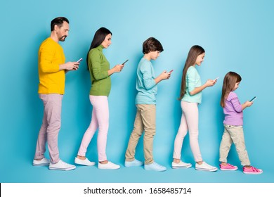 Full length body size profile side view of nice attractive focused cheerful big full family pre-teen kids using 5g internet online isolated on bright vivid shine vibrant blue color background