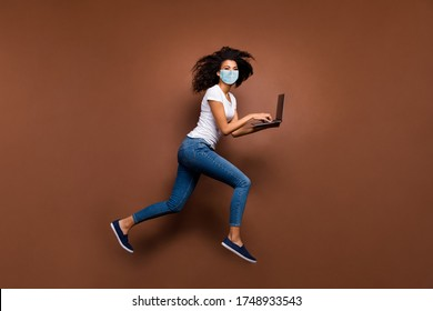 Full length body size profile side view of her she attractive healthy wavy-haired girl wearing gauze safety mask jumping using laptop running stop cov ncov-2 isolated dark brown color background