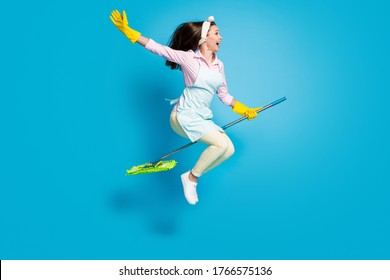 Full length body size profile side view of her she nice attractive funky childish comic maid jumping riding broom like horse isolated on bright vivid shine vibrant blue color background
