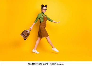 Full length body size profile side view of her she attractive cheery intellectual girl nerd jumping going back to school new grade semester isolated bright vivid shine vibrant yellow color background