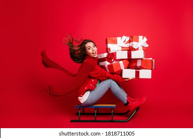 Full length body size profile side view of attractive glad cheerful girl elf Santa assistant riding sledge delivering giftboxes bargain isolated bright vivid shine vibrant red color background