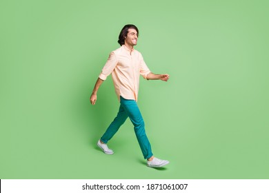 Full length body size profile side view of nice cheery guy wearing casual clothes walking isolated over bright green color background