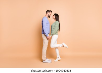 Full length body size profile side view of nice amorous couple soulmates meet holding hands isolated on beige pastel color background