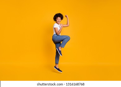 Full length body size side profile photo jumping high beautiful she her lady yelling loud voice legs fists hands arms up win wearing casual jeans denim white t-shirt clothes isolated yellow background