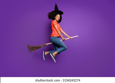 Full length body size side profile photo of cheerful funny witch riding a broomstick expressing emotions wearing orange t-shirt jeans denim cap headwear flying jumping color violet background