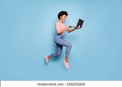 Ganzes Ganzkörpergrößenfoto von ziemlich fröhlich süßem, nettem, charmantem Jugendlicher, der vor dem Laptop ein Jeans mit Jeans trägt, das gestreifte Hemd einzeln auf pastellblauem Hintergrund