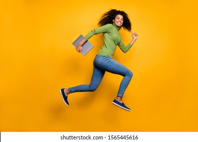 Full length body size side profile photo of cheerful positive cute pretty girlfriend smile toothy in jeans denim footwear holding laptop isolated vivid color background running jumping