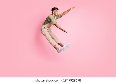 Full length body size side profile photo of guy flying back in windy weather isolated on pastel pink color background