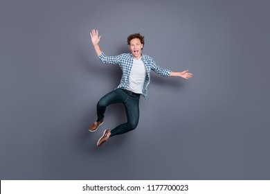 Full length body size of stylish trendy nice handsome attractive guy with wavy hair in casual checkered shirt and jeans, jumping in air, fooling, dancing. Isolated over grey background