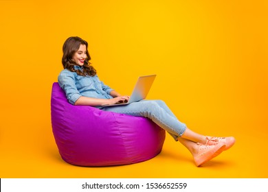 Full length body size turned photo of cheerful positive cute nice attractive blogger browsing through her laptop in search of new information isolated over yellow vibrant color background