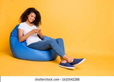 Full length body size turned photo of cheerful curly wavy brown haired positive girl browsing through her phone answering in comments of her repost isolated over vivid color background