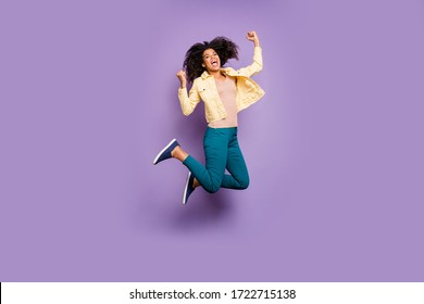 Full length body size turned photo of cheerful rejoicing girl jumping with victorious event in pants trousers shouting isolated pastel color background violet