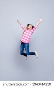 Full length body size vertical photo blond haired she her little cheerleader laugh laughter jump high achievement wear casual jeans pink plaid checkered shirt outfit clothes isolated grey background