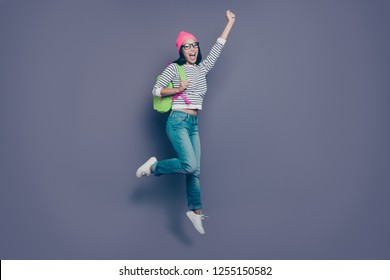 Full length body size view of nice lovely attractive cheerful cheery childish positive girl wearing striped pullover jeans denim raising hand up isolated over violet purple pastel background