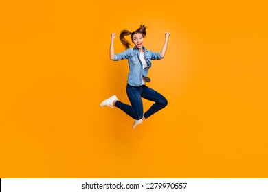 Full length body size view of nice attractive strong slim sporty fit cheerful cheery playful school girl flying in air having fun triumph isolated over bright vivid shine yellow background