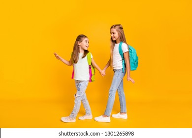 Full length body size view of two nice attractive cheerful smart clever pre-teen girls with colorful backpacks holding hands back to school isolated over bright vivid shine yellow background