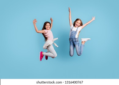 Full length body size view of two people nice lovely attractive charming cheerful crazy careless straight-haired pre-teen girls rejoicing overjoy cool day isolated over blue pastel background