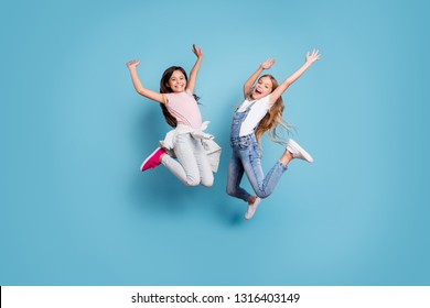 Full length body size view of two people nice-looking crazy lovely attractive cheerful carefree straight-haired pre-teen girls having fun great weekend time overjoy isolated over blue background