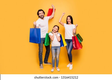Full length body size view portrait of nice attractive trendy cheerful people holding in hands bags with new clothes having fun rejoice isolated over shine vivid pastel yellow background