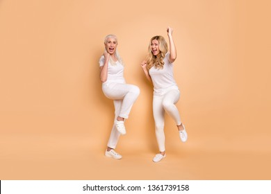 Full length body size view portrait of nice cool attractive charming slender slim fit cheerful cheery ecstatic ladies wearing white t-shirt having fun isolated on beige pastel background
