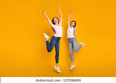Full length body size view portrait of nice charming attractive cheerful overjoyed slim fit thin straight-haired girls having fun rejoice isolated on bright vivid shine yellow background