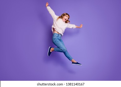 Full length body size view photo cute energetic active teen teenager youth have holidays scream shout rejoice candid content isolated pullover denim blue sneakers raise hands arms purple background