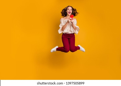 Full length body size view portrait of nice attractive slim fit thin glad cheerful cheery wavy-haired lady using modern technology device gadget isolated over bright vivid shine yellow background