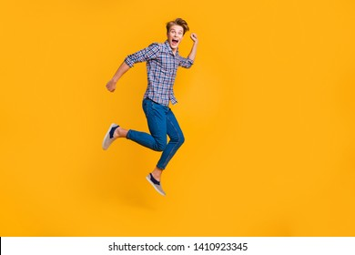 Full length body size view portrait of nice attractive cheerful cheery optimistic guy in checked shirt having fun running fast hurry rush isolated over bright vivid shine yellow background