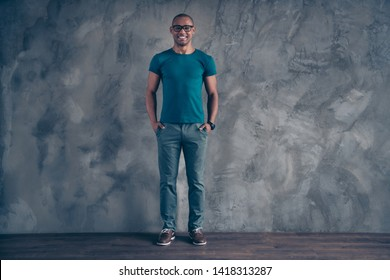 Full length body size view portrait of his he nice lovely cool attractive sporty good-looking cheerful cheery guy wearing blue t-shirt pants modern look isolated over gray industrial concrete wall