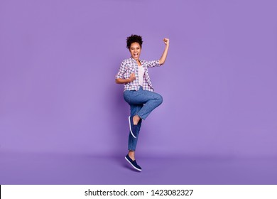 Full length body size view photo delighted fun funny funky lady free time dream dreamy scream yeah top-knot luck lucky raise fists beautiful stylish plaid shirts jeans isolated purple background
