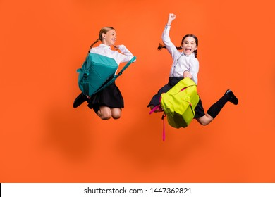 Full length body size view of two person nice attractive charming ecstatic cheerful cheery pre-teen girls having fun holiday 1 September isolated on bright vivid shine orange background