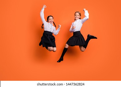 Full length body size view of two person nice attractive lovely charming cute ecstatic overjoyed cheerful cheery pre-teen girls having fun rejoice isolated on bright vivid shine orange background